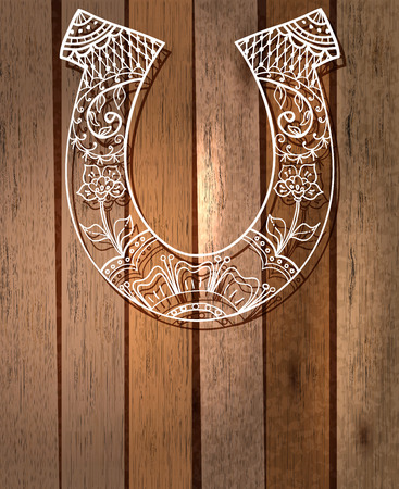 horse shoe: horseshoe with floral ornament, lucky symbol over wood background