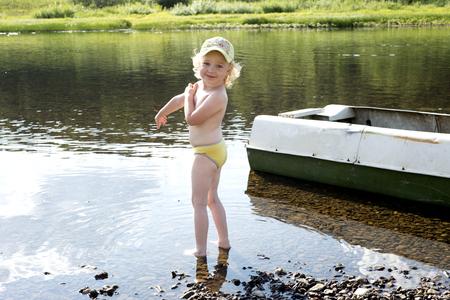 mignonne petite fille: Petite fille sur la rivière, sourire petit bébé debout dans l'eau