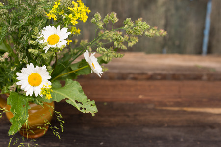 Bunch of chamomile flowers, beautiful bouquet over wood background