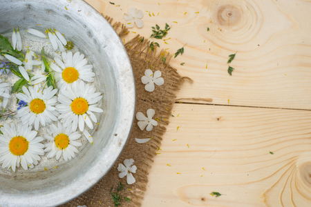chamomile flowers in a cup, beautiful flowers over wood background