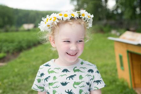 Mignon petite fille souriante dans la couronne de camomille, heure d'été