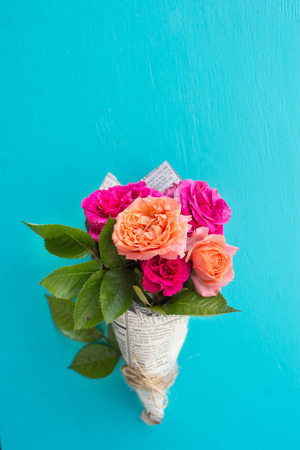 Fresh pink and orange roses in paper cover over blue background, still life background