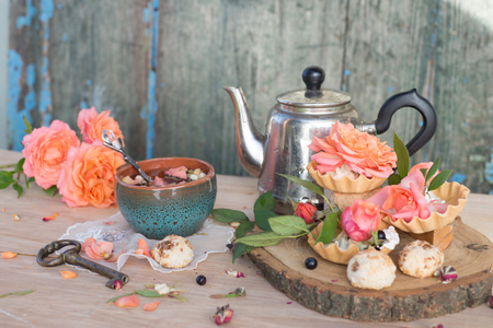 Herbal tea with fresh and dry rose petals over wooden background, stilllife background Stock Photo
