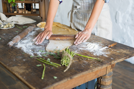 Dough for pasta rolling with wooden rolling pin over wooden kitchen table by hands Stock Photo
