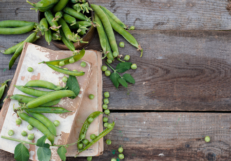 green peas on rustic wooden background with old books Stock Photo