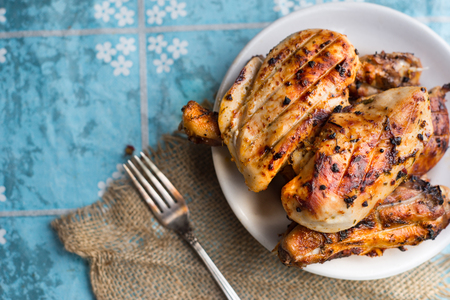 Roasted chicken breast over blue background