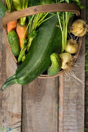 Fresh vegetables in old brown basket over wooden background Banco de Imagens