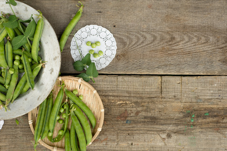 green peas on rustic wooden background in old metal plate