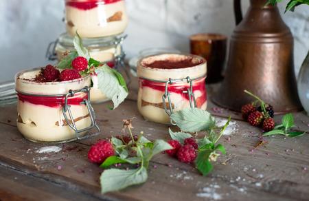 Tiramisu cake in glass jar with red raspberry, still life