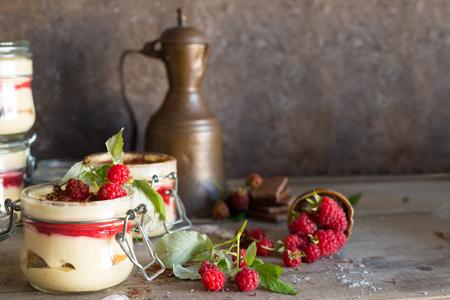 Tiramisu cake in glass jar with red raspberry, dark still life