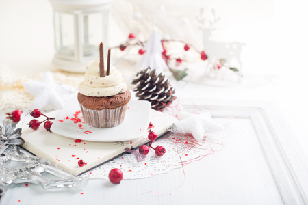 Cupcake with white cream over Christmas background Stock Photo
