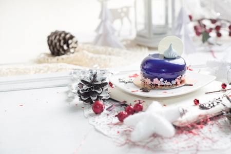 French mousse cake covered with violet glaze over Christmas background,  Violet modern European dessert 스톡 콘텐츠