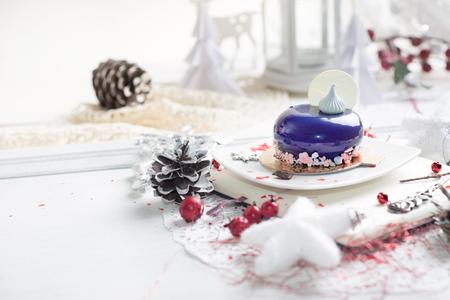 French mousse cake covered with violet glaze over Christmas background,  Violet modern European dessert 版權商用圖片
