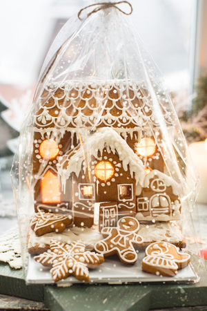 Beautiful background with gingerbread house, modern food still life, Christmas holiday card, rustic background Stock Photo