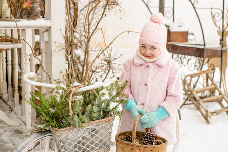 Little girl holding a basket with cones, winter season, beautiful exterior