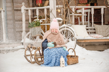 Little girl sits on a sled, wrapped in a blanket, snowfalling,eyes are squinting