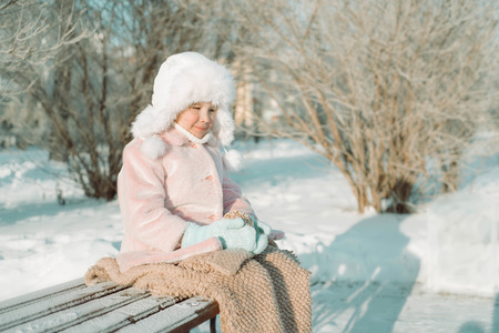 Little girl with Christmas toy sitting outside in the park, with smile on face, joyful child