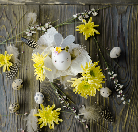 Easter card, holiday background with eggshell rabbit and flowers over wooden background