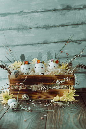 Easter background, homemade eggshell bunnies and yellow chrysanthemum in wooden box for beautiful holiday design of cards