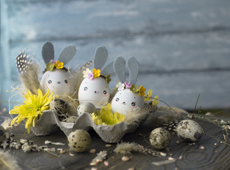 Easter background, homemade eggshells rabbits and yellow chrysanthemum in cardboard boxes over wooden background for beautiful holiday card design