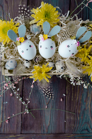 Easter background, homemade eggshell bunnies and yellow chrysanthemum in wooden box for beautiful holiday design of cards Imagens - 119575782