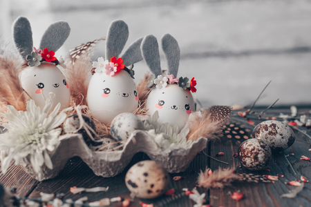 Easter background, homemade eggshells rabbits and yellow chrysanthemum in cardboard boxes over wooden background for beautiful holiday card design Stockfoto - 119575784