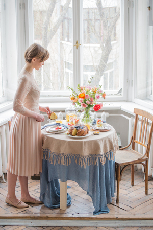Tea time, Beautiful woman with tea pot, beautiful flower bouquet, cake, arranged on table