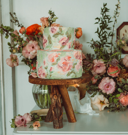 Cake on wooden stand with flowers, beautiful vintage room