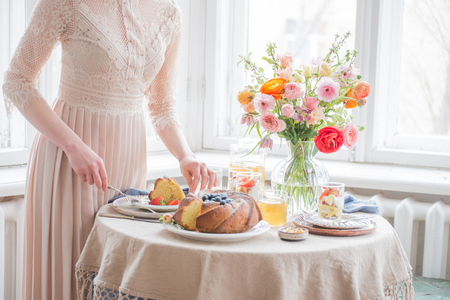 Tea time, Beautiful woman hands with tea pot, beautiful flower bouquet, cake, arranged on table 写真素材