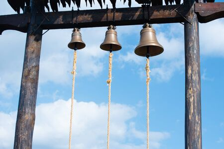 Three metal bells on wooden crossbar over blue sky