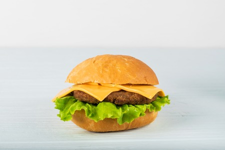 Craft beef burger on wooden table isolated on white background
