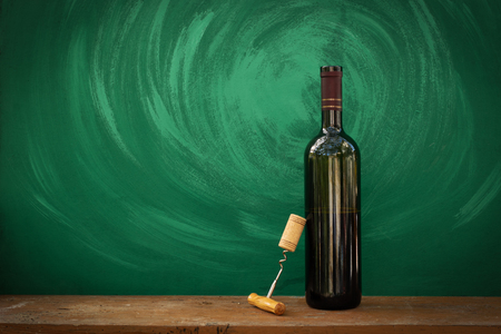 Bottle and glass with red wine on wooden background 写真素材