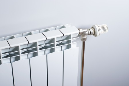 A White heating radiator on the wall. Imagens - 114390076