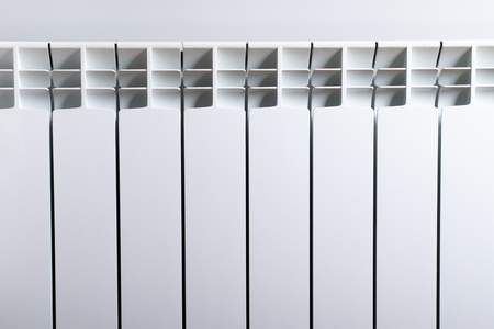 A White heating radiator on the wall. Imagens - 114390078