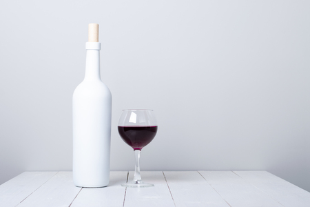 Red wine bottle on a white wooden background