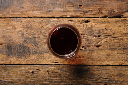 Glass of red wine on wooden table. View from top 写真素材