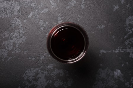 Glass of red wine on dark gray table. View from top 写真素材
