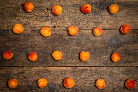 Delicious ripe apricots in a wooden bowl on the table close-up. Horizontal view from above