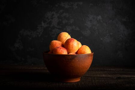 fresh apricots in a basket on a wooden table