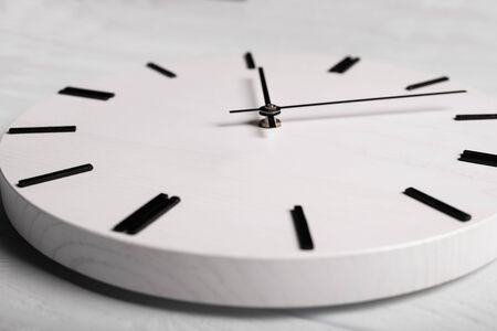 wall clock at wooden white background texture
