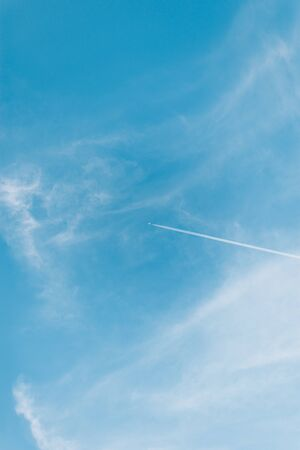 Beautiful picture of white plane flying with trail in blue sky