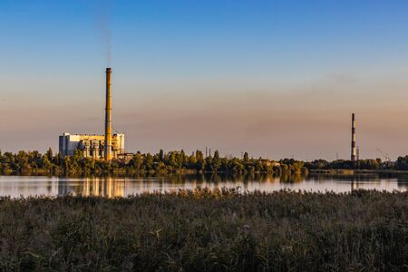 Old Waste incinerator plant with smoking smokestack on Lake bank. The problem of waste processing