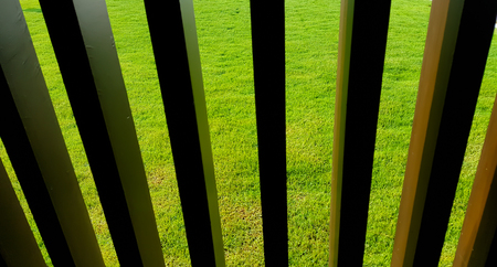 background with old wooden fence and green grass Stock Photo