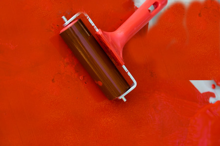 paint can: Red roller painting the white wall Stock Photo