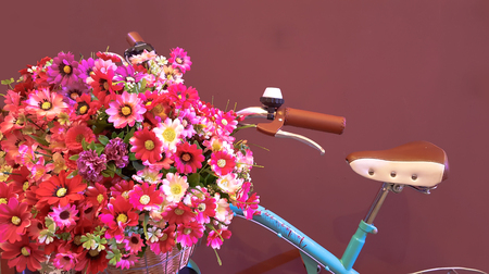 Vintage bicycle with basket with peony flowers near