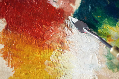 Palette of wood on which a palette knife applied oil paint yellow, red, green and white.