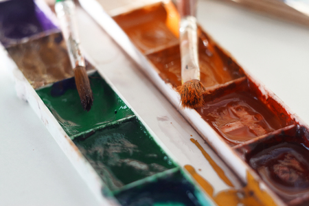 Art brushes and an old watercolor palette lie on a white background on a Sunny day