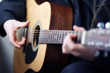 A man in dark clothes playing acoustic wooden six-string guitar beautiful melodies and songs Reklamní fotografie