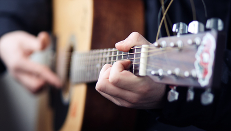 A man in black clothes playing a rock song on a beautiful wooden acoustic guitar, clamping chords