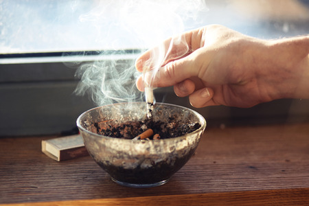 On the windowsill is a dirty ashtray with cigarette butts and a box of matches. The hand of man shakes off the ashes with a cigarette in the ashtray.